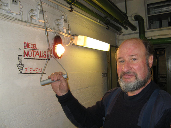 """Unser Schirrmeister Klaus Griem an einem Notaus-Hebel für den Dieselmotor, den er konstruiert und mit Helfern unseres Ortsverbandes in den 1970er Jahren in Bunkern im Bezirk Hamburg-Nord eingebaut hatte. Damals war ein Motor beim Starten """"rückwärts"""" angelaufen und konnte nicht gestoppt werden, da er Luft durch den Auspuff ansaugte und die Abgase über den Lufteinlass in den Maschinenraum blies."""