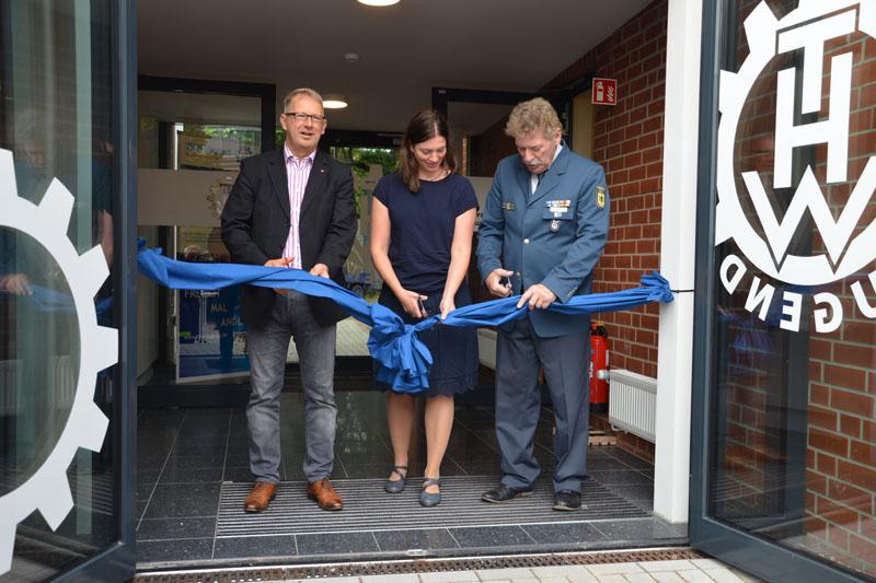 Mit Johannes Kahrs und Kristin Nestner von der BImA durchschnitt der Ortsbeauftragte anschließend eine Schleife am Eingang des Neubaus als symbolische Öffnung des Gebäudes.