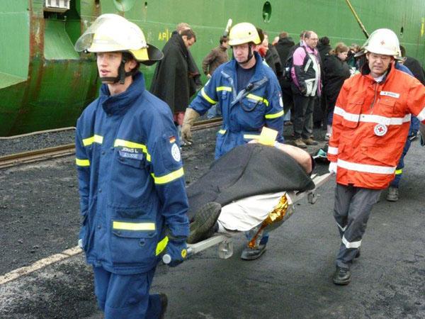 """Helfer des Ortsverbandes Hamburg-Nord beteiligen sich an dem Transport der """"Verletzten"""" vom Schiff zu den Rettungswagen."""