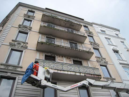 Entfernen des lockeren Mauerwerks mittel Hubsteiger von der Hausfassade.