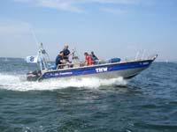 Mehrzweckarbeitsboot mit absenkbarer Bugklappe (motorisiert mit 2 x 70 PS) vom Typ Faster 650 Cat einsetzbar bis Windstärke 6 und 2m Wellenhöhe. Die belastbare Bugklappe dient zur Übernahme von Menschen, Tieren und Ausrüstung.