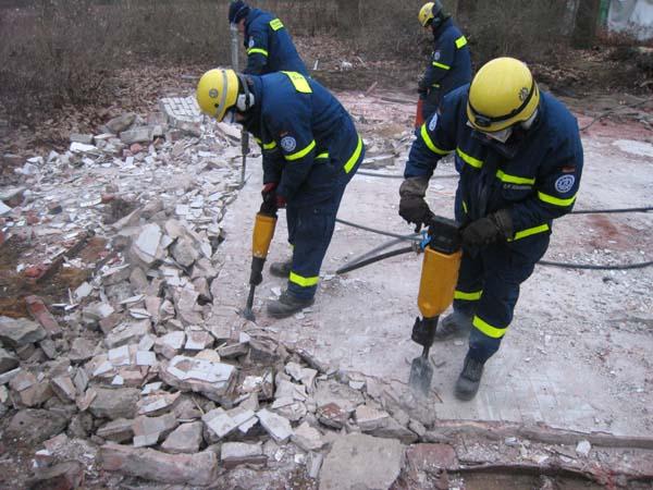 Mit den Aufbrechhämmern der Fachgruppe Räumen wird die Bodenplatte zerkleinert.